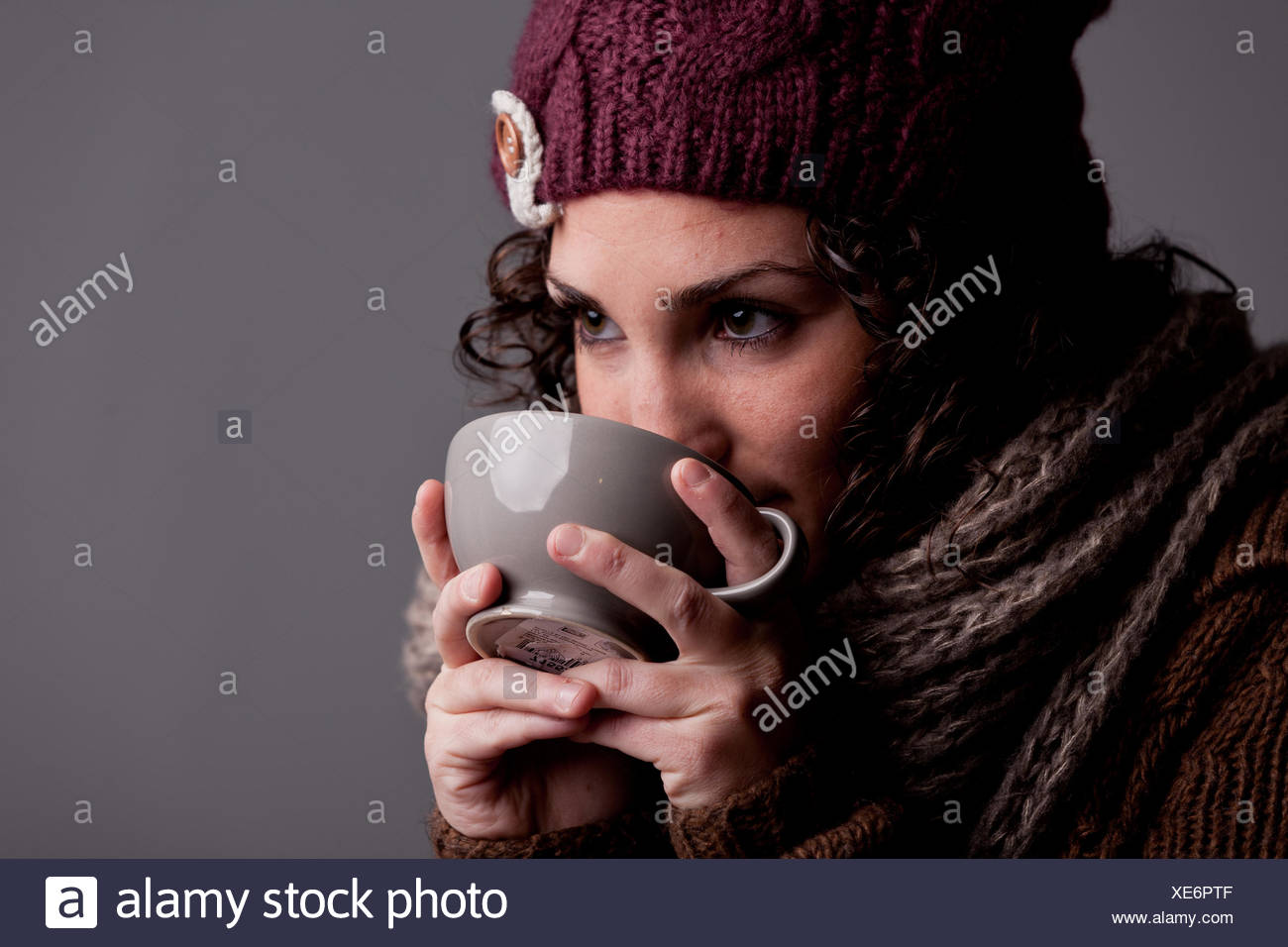 15058a3e77f it s winter and this girl with wool hat and scarf drinks a hot chocolate or  hot tea or milk from a big mug and she s happy