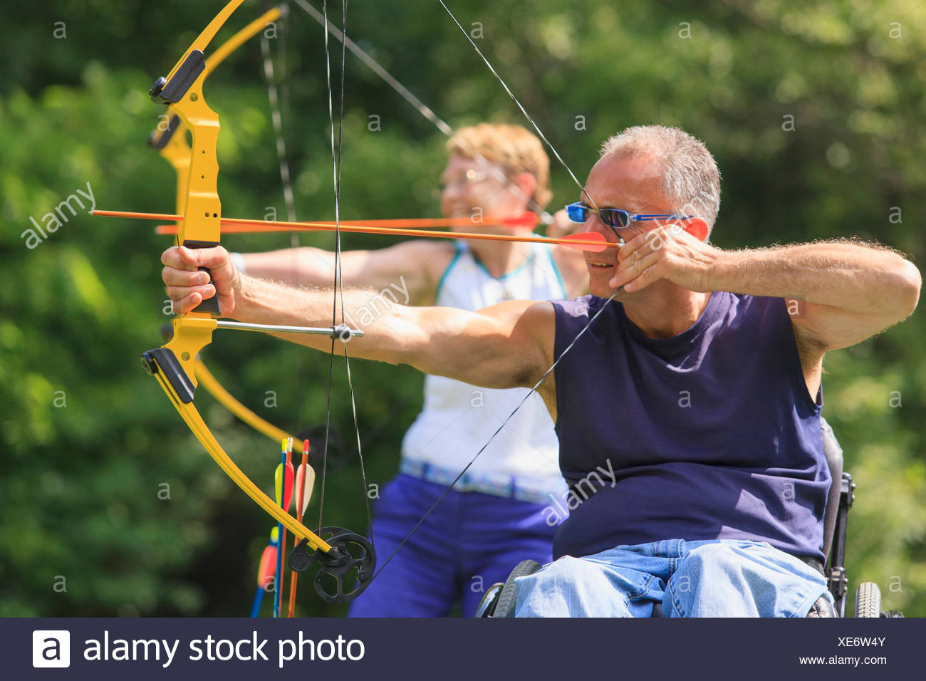 Man with spinal cord injury and woman with prosthetic leg aiming arrows at target - Stock Image