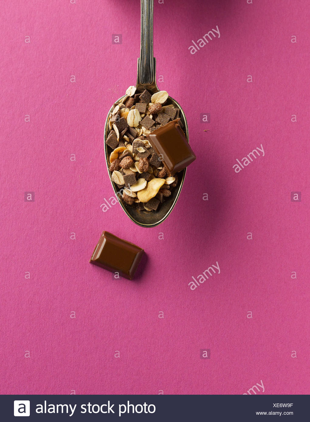 Cereal and chocolate in spoon on pink background - Stock Image