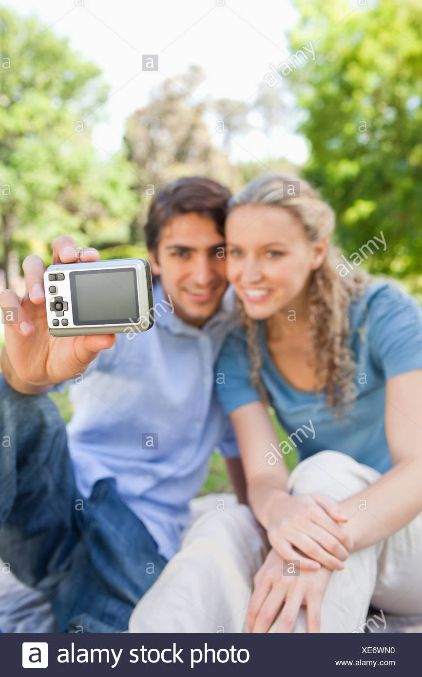 Camera being used by a couple to take pictures in the park - Stock Image