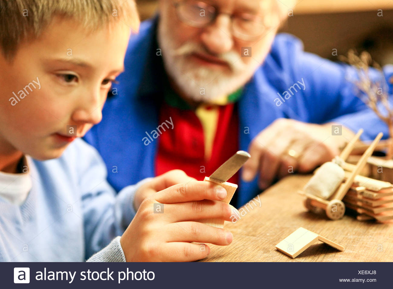 Grandfather and grandson making wooden craft together - Stock Image