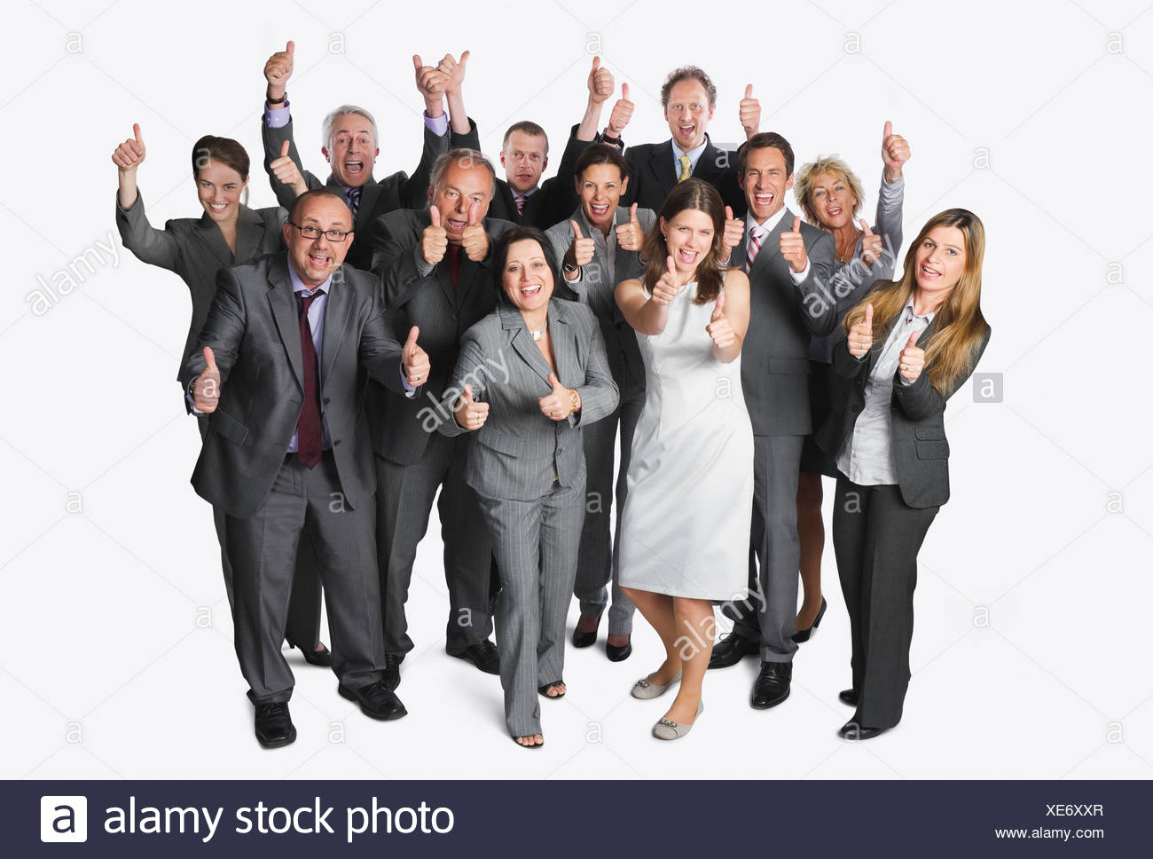 Large group of business people showing thumbs up against white background - Stock Image