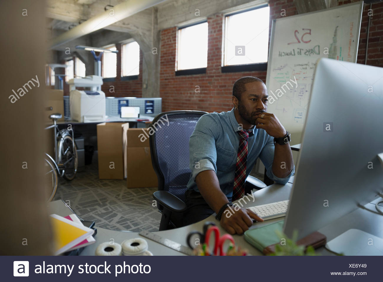 Entrepreneur using computer in new office - Stock Image