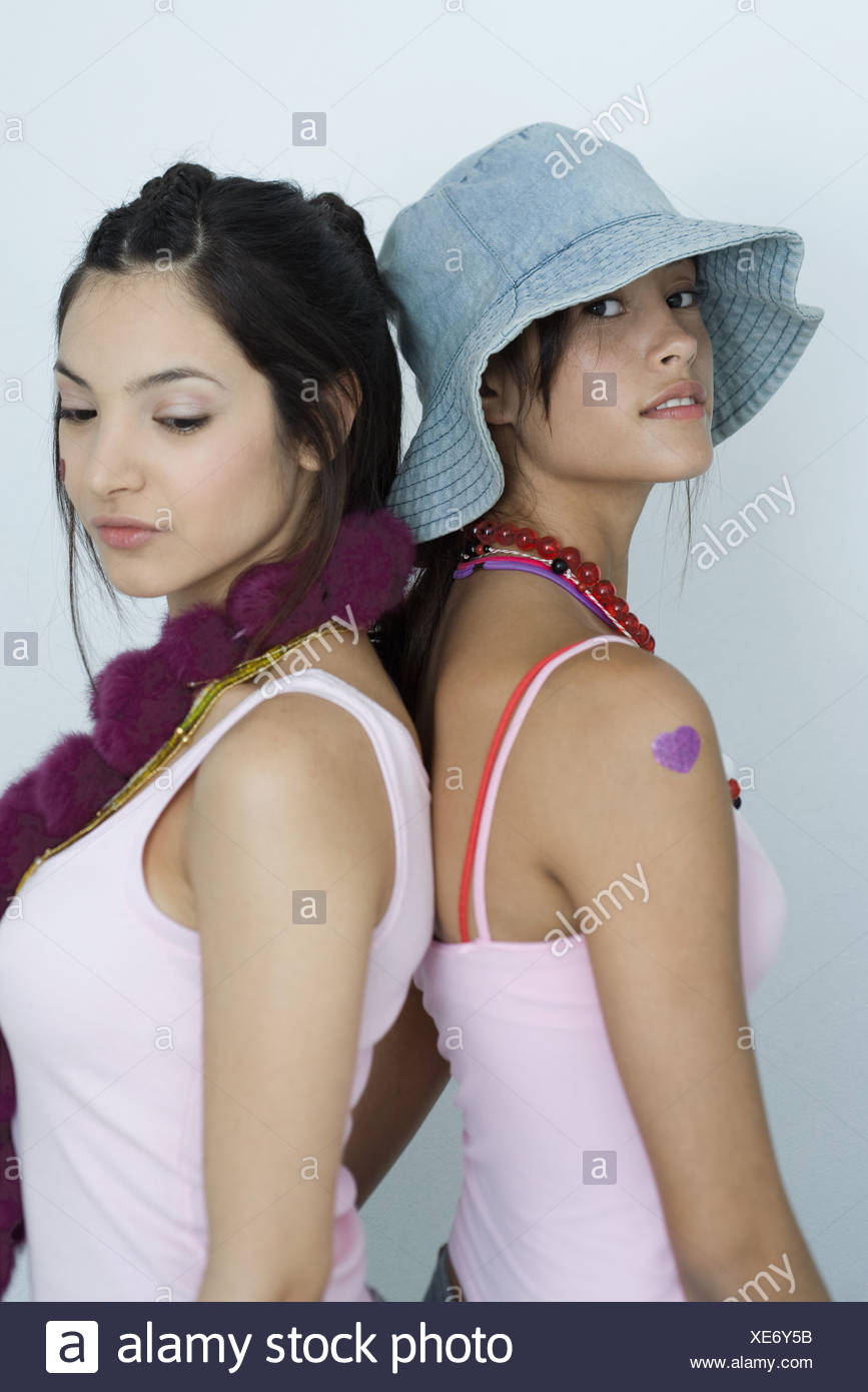 Two young female friends, standing back to back, one looking at camera, the other looking down, waist up, portrait - Stock Image