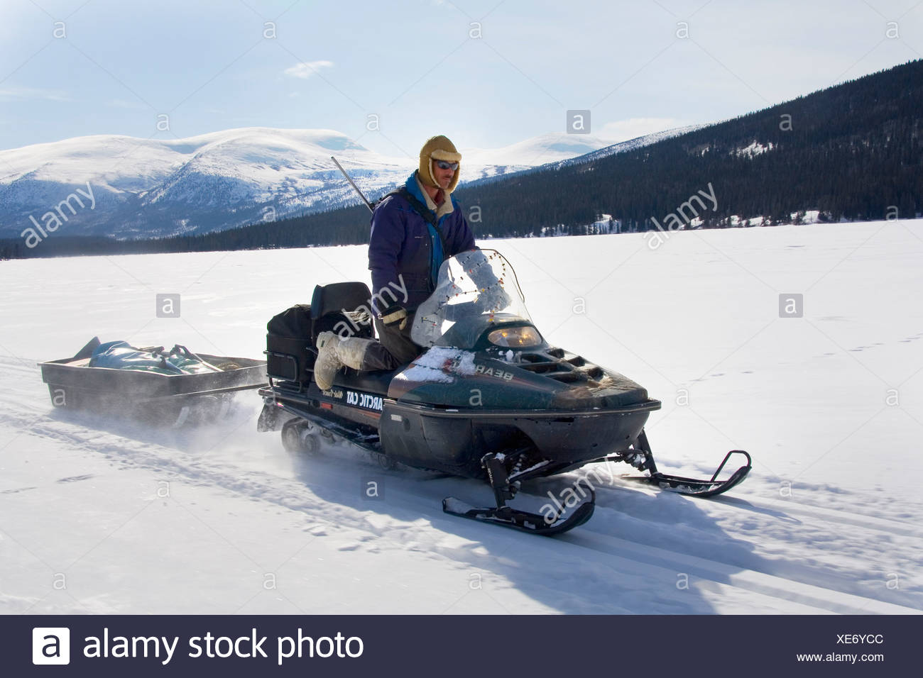 Hunter driving a snowmobile or skidoo, Yukon Territory, Canada, North America - Stock Image