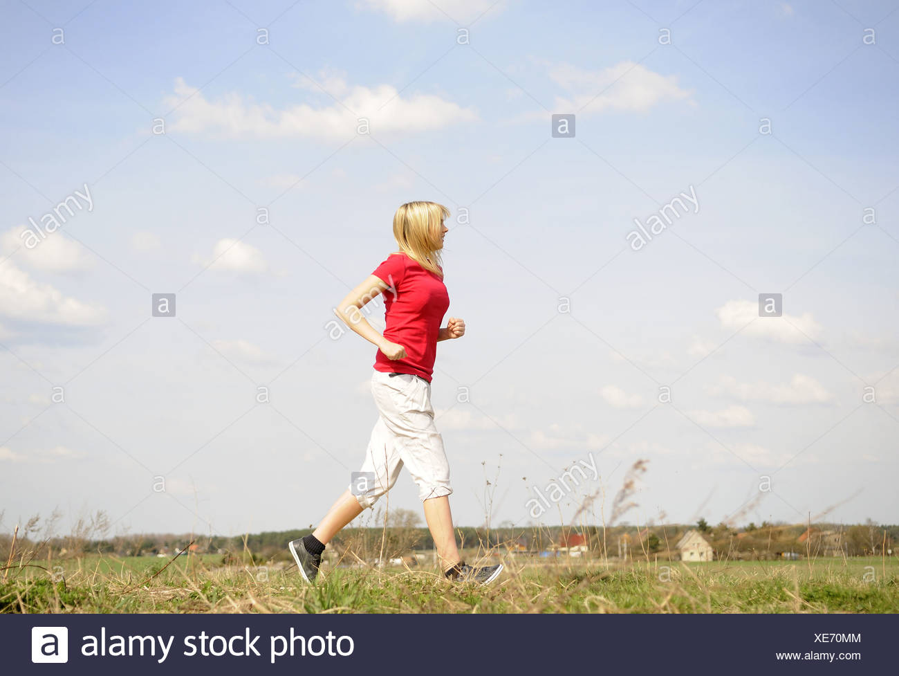 young woman jogging on a dirt road - Stock Image