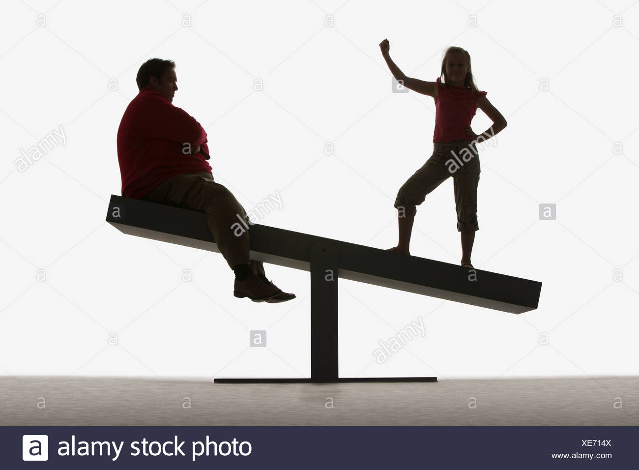 Man and girl on ends of a plank - Stock Image