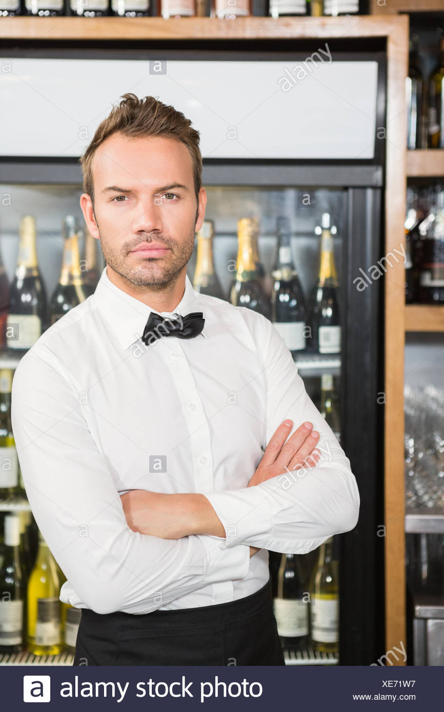 Handsome barman crossing his arms - Stock Image