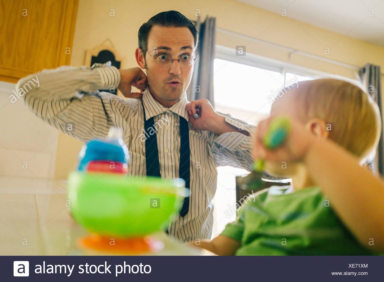 Father and young son in kitchen, father putting on neck tie whilst son eats breakfast - Stock Image