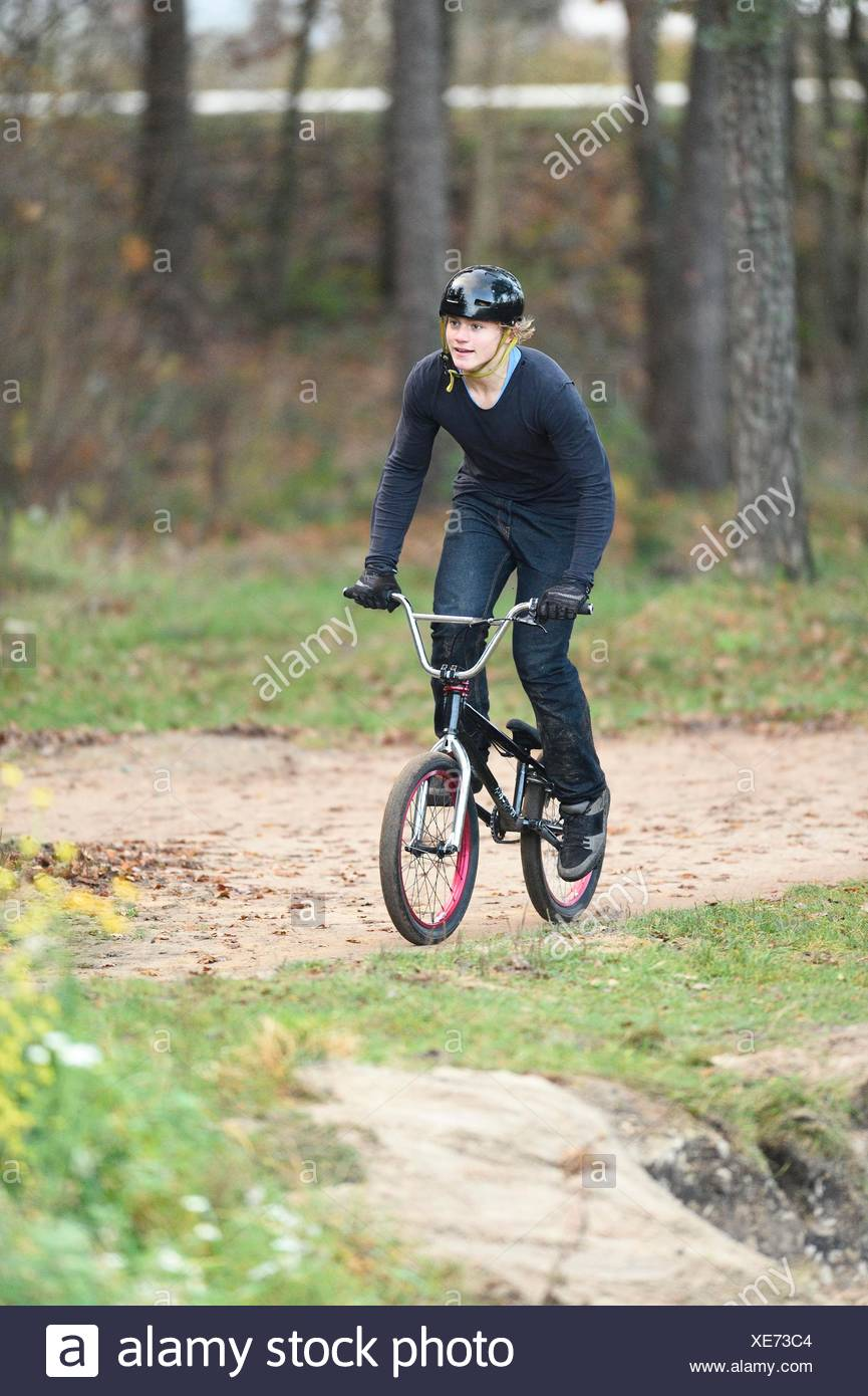 Teenager with bmx bike in forest - Stock Image