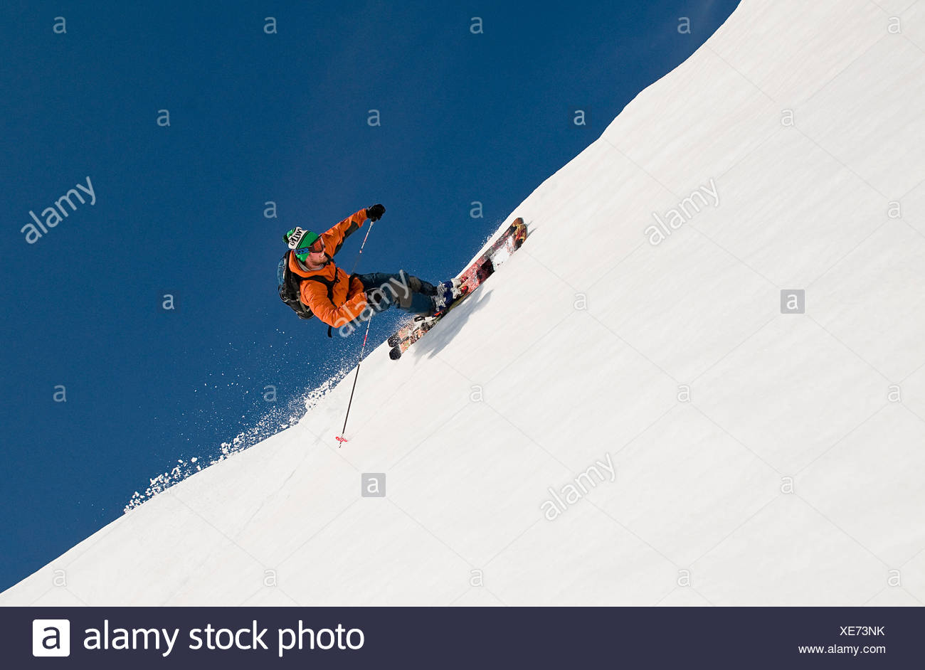 A skier rides the rim of a natural half-pipe while heli-skiing near Juneau, Alaska - Stock Image