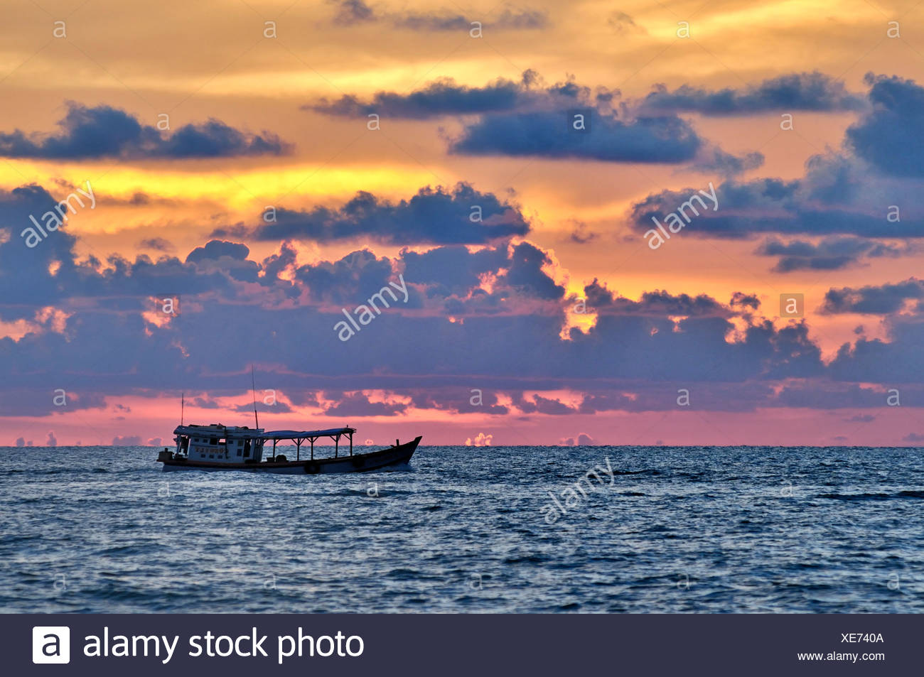 Fishing boat at atmospheric sunset, sea, Phu Quoc, Vietnam, Asia - Stock Image