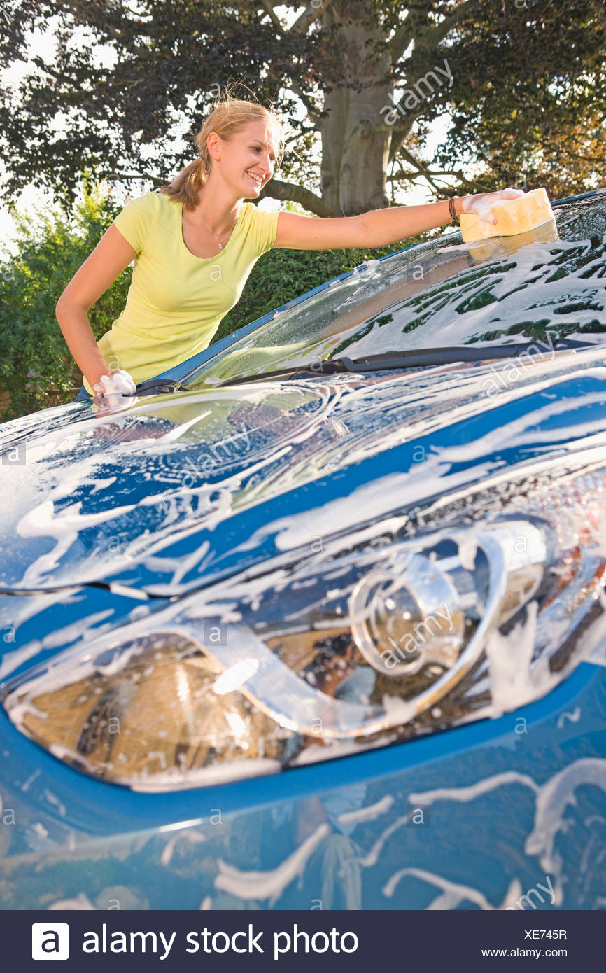 Woman Cleaning Car At Home - Stock Image