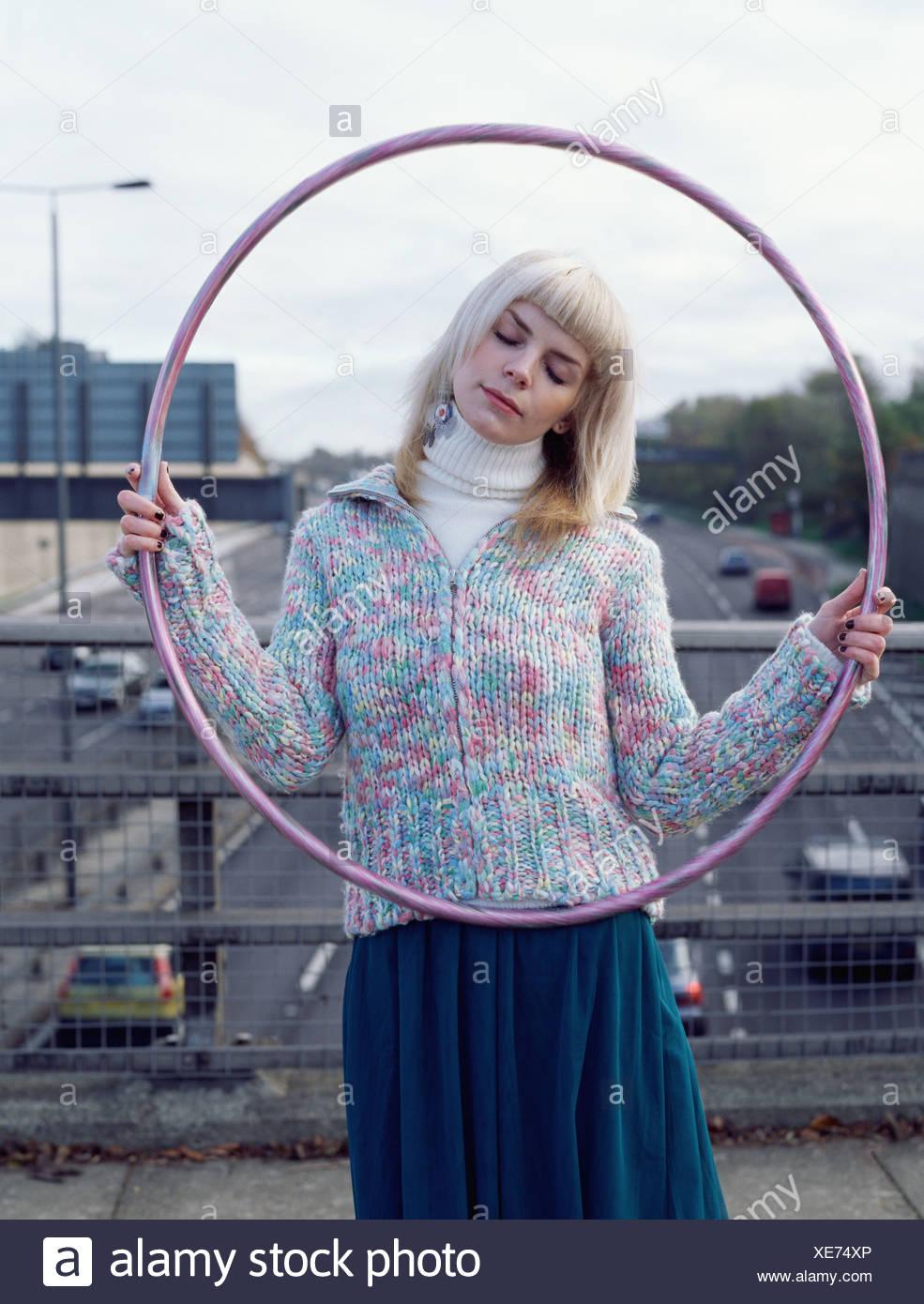 Woman holding hula hoop on motorway bridge - Stock Image