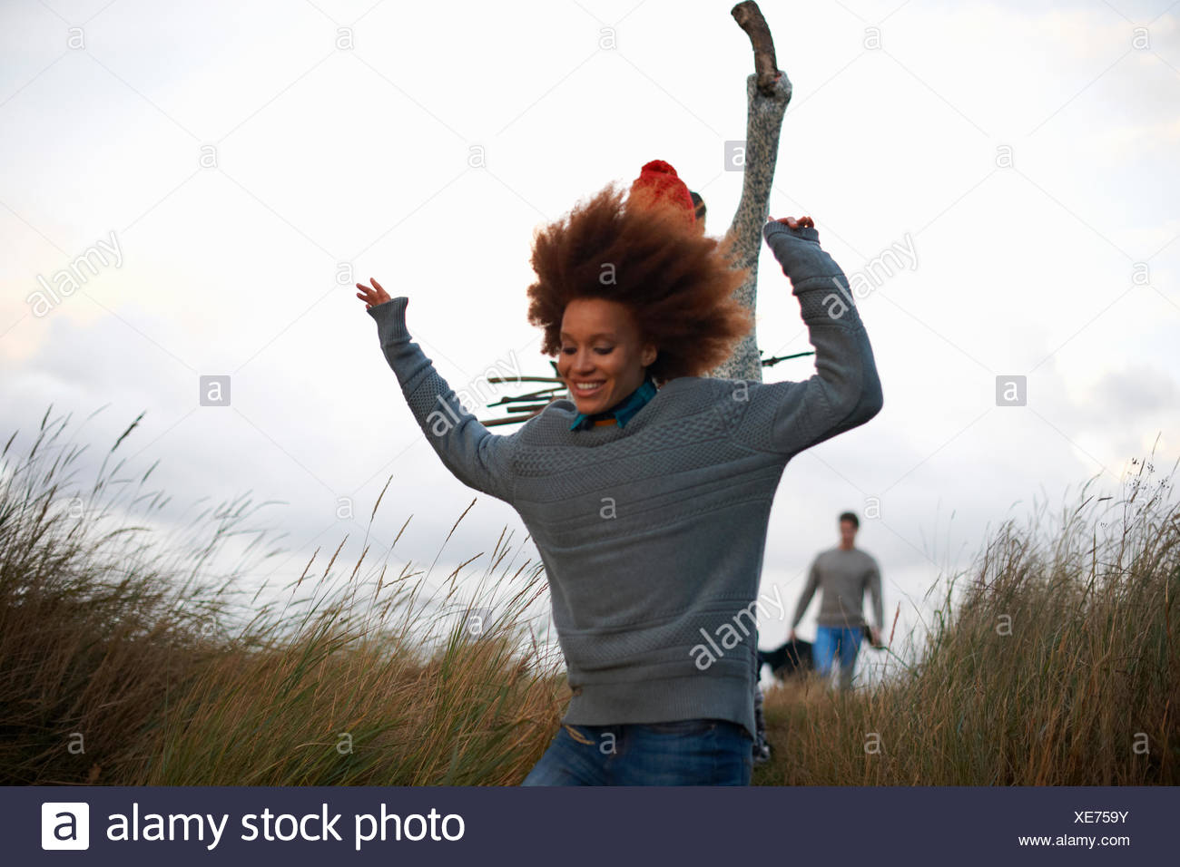 Young adults running in coastal dunes - Stock Image