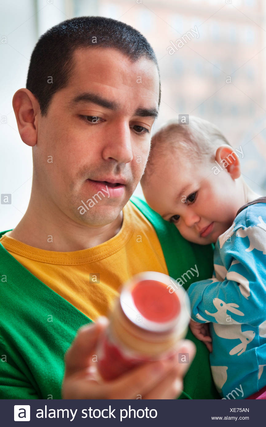 Father holding his daughter (0-11 months) and a jar of baby food - Stock Image
