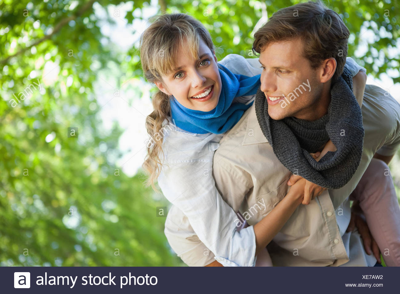 Cute woman smiling at camera in the park while getting a piggy back - Stock Image