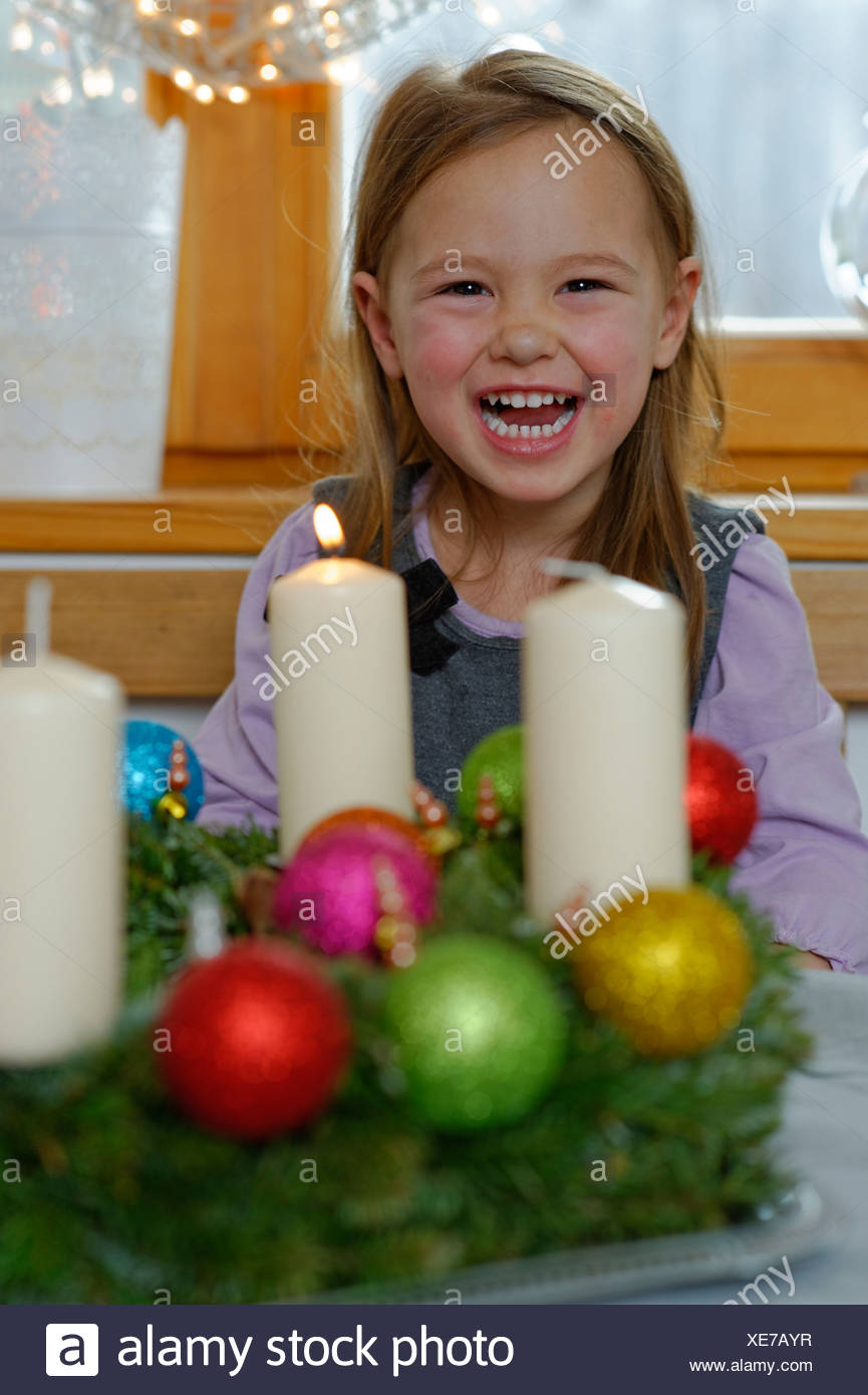 Girl enjoying the first lit candle on the Advent wreath - Stock Image