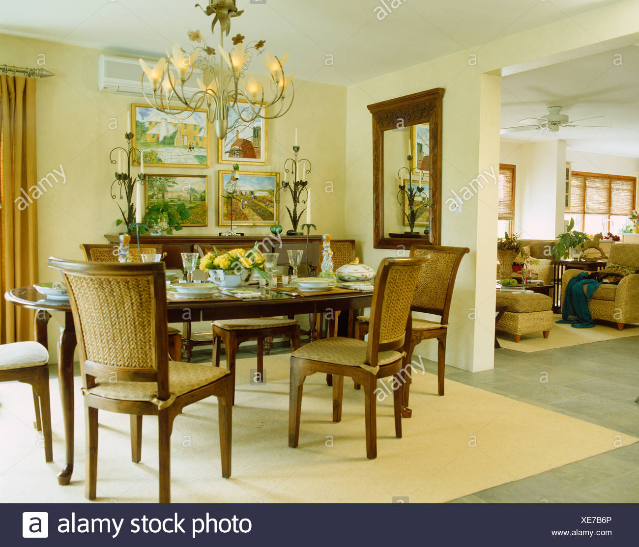 Ornate Metal Chandelier Above Upholstered Chairs And Dark Wood Table Set  For Lunch In Yellow Open Plan Dining Room