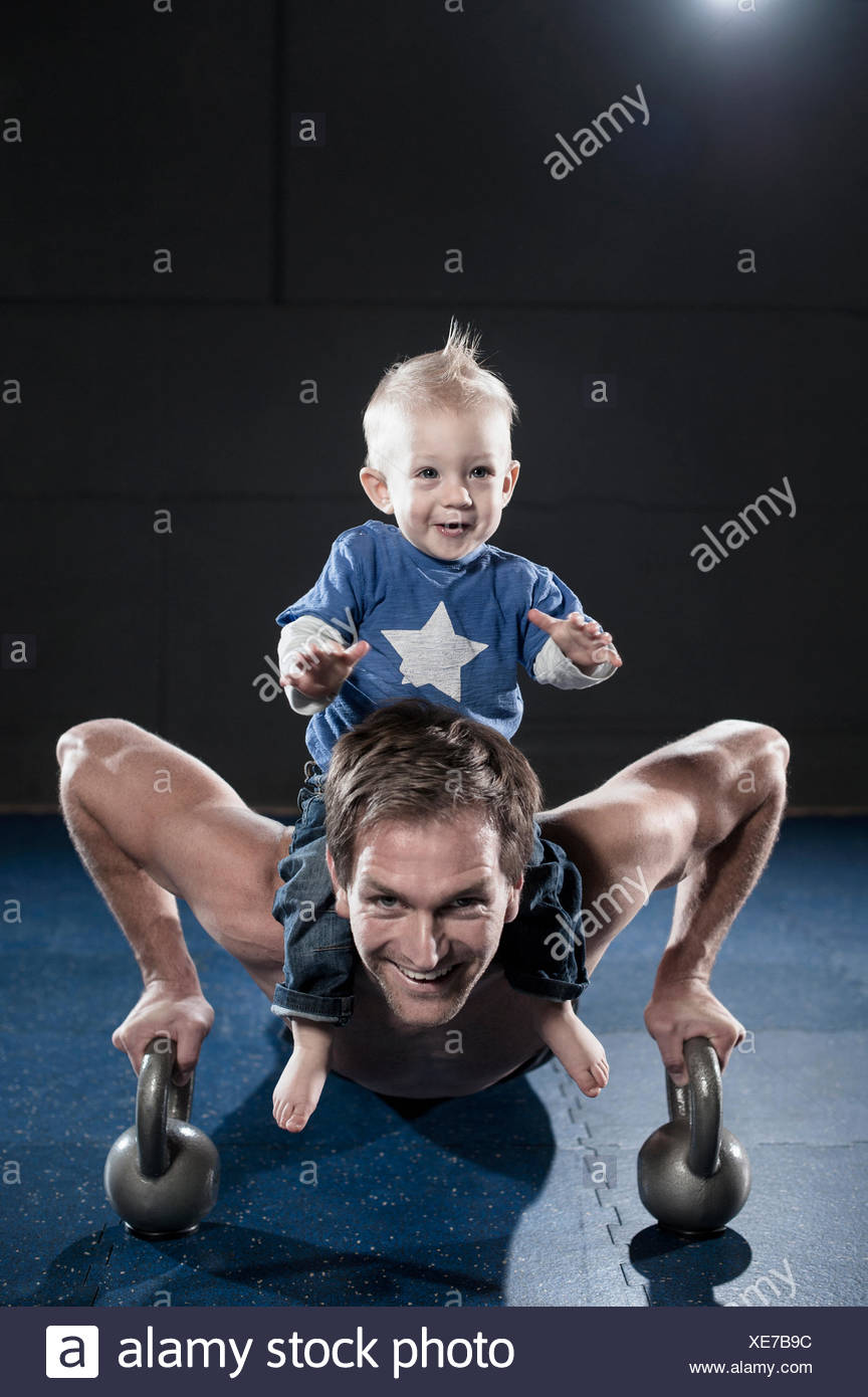 Portrait of smiling athlete doing push ups carrying son on shoulder, Bavaria, Germany - Stock Image