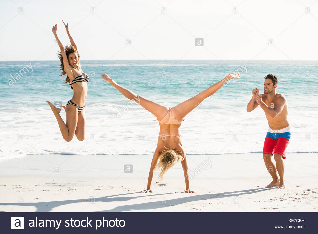 Beautiful excited friends jumping on the beach - Stock Image