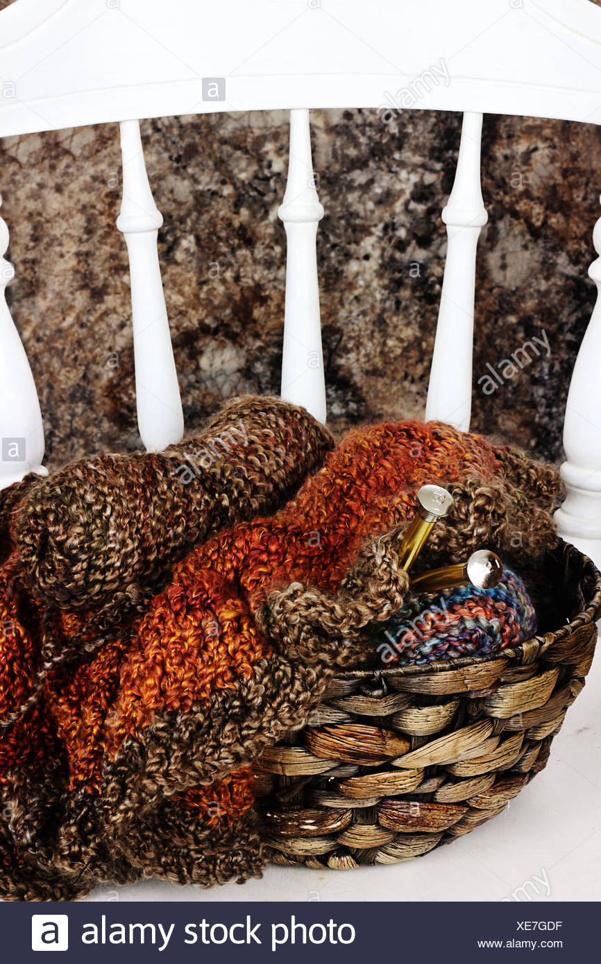Basket filled with crocheted blanket, soft skeins of yarn needlework and knitting needles sitting on old antique kitchen chair - Stock Image