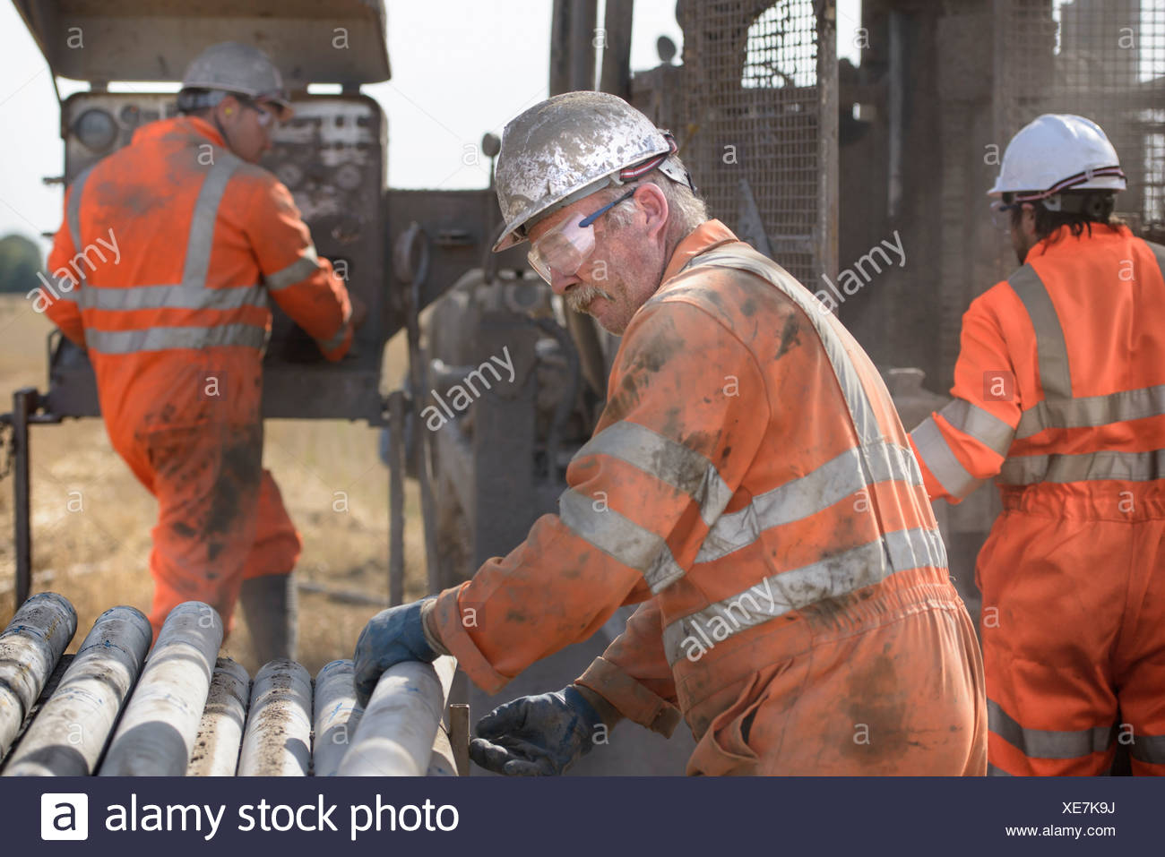 Workers in hard hats operating drilling rig Stock Photo