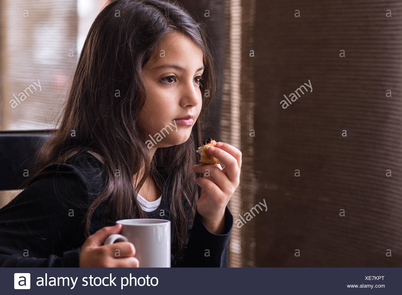 Girl sitting in cafe with a cup of hot chocolate and cake - Stock Image