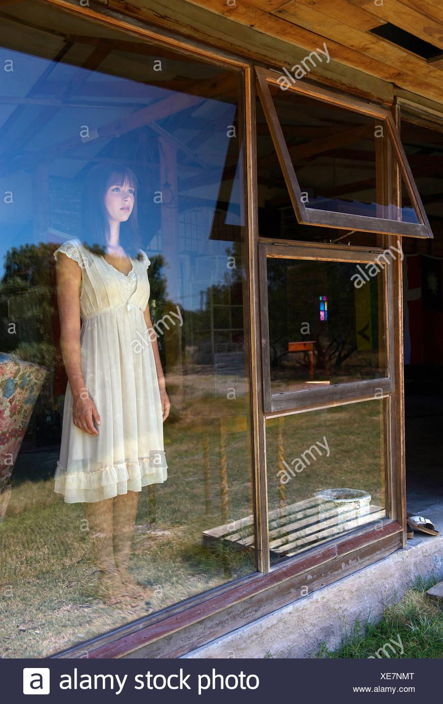 Teenage girl standing in window - Stock Image