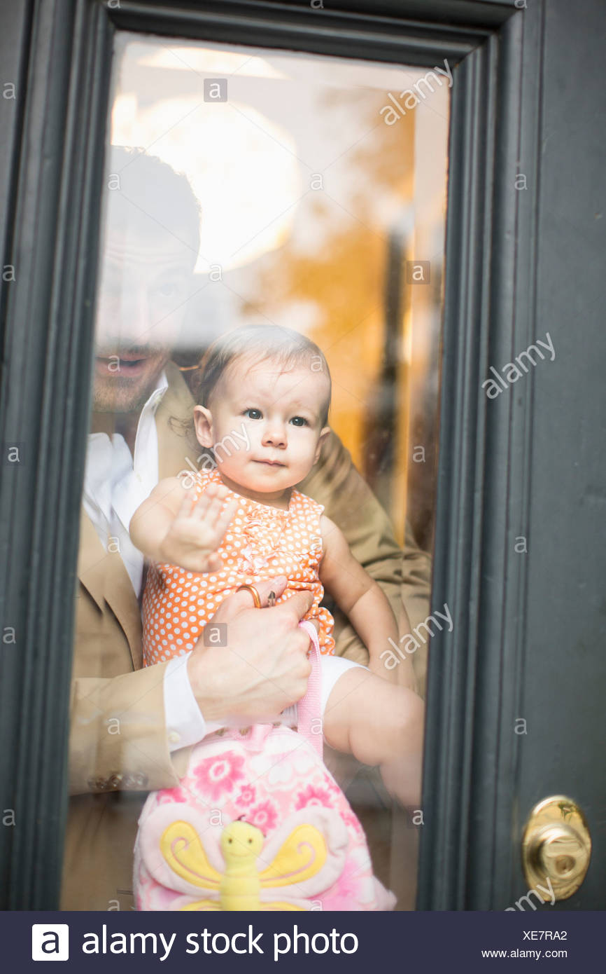 Man holding baby looking through front door - Stock Image