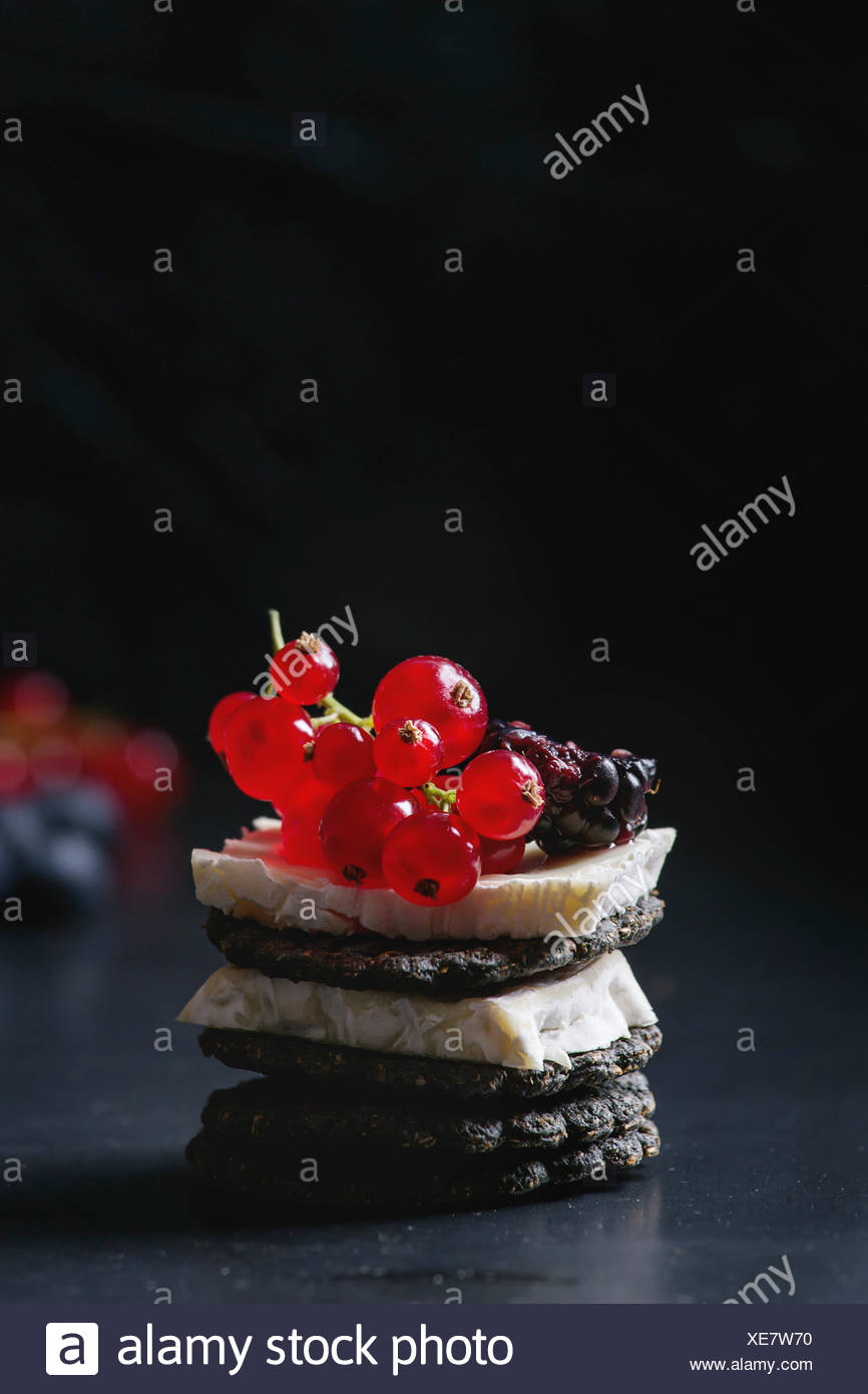 Black charcoal crackers with camembert brie cheese and berries blueberry, dewberry, red currant and sliced figs, served on vintage tray over dark meta - Stock Image