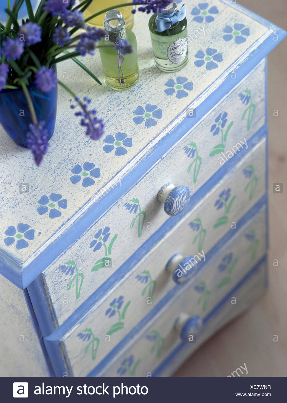 Close-up of a painted chest of drawers with a stenciled floral pattern - Stock Image