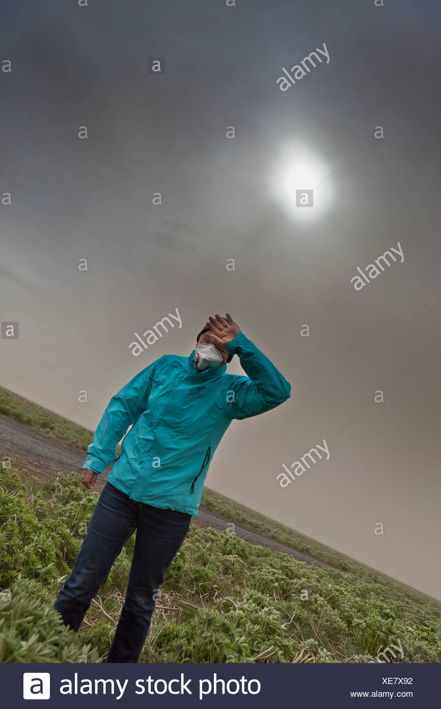 Woman wipes the ash from her eyes from Grimsvotn Volcanic Eruption in the Vatnajokull Glacier, Iceland - Stock Image