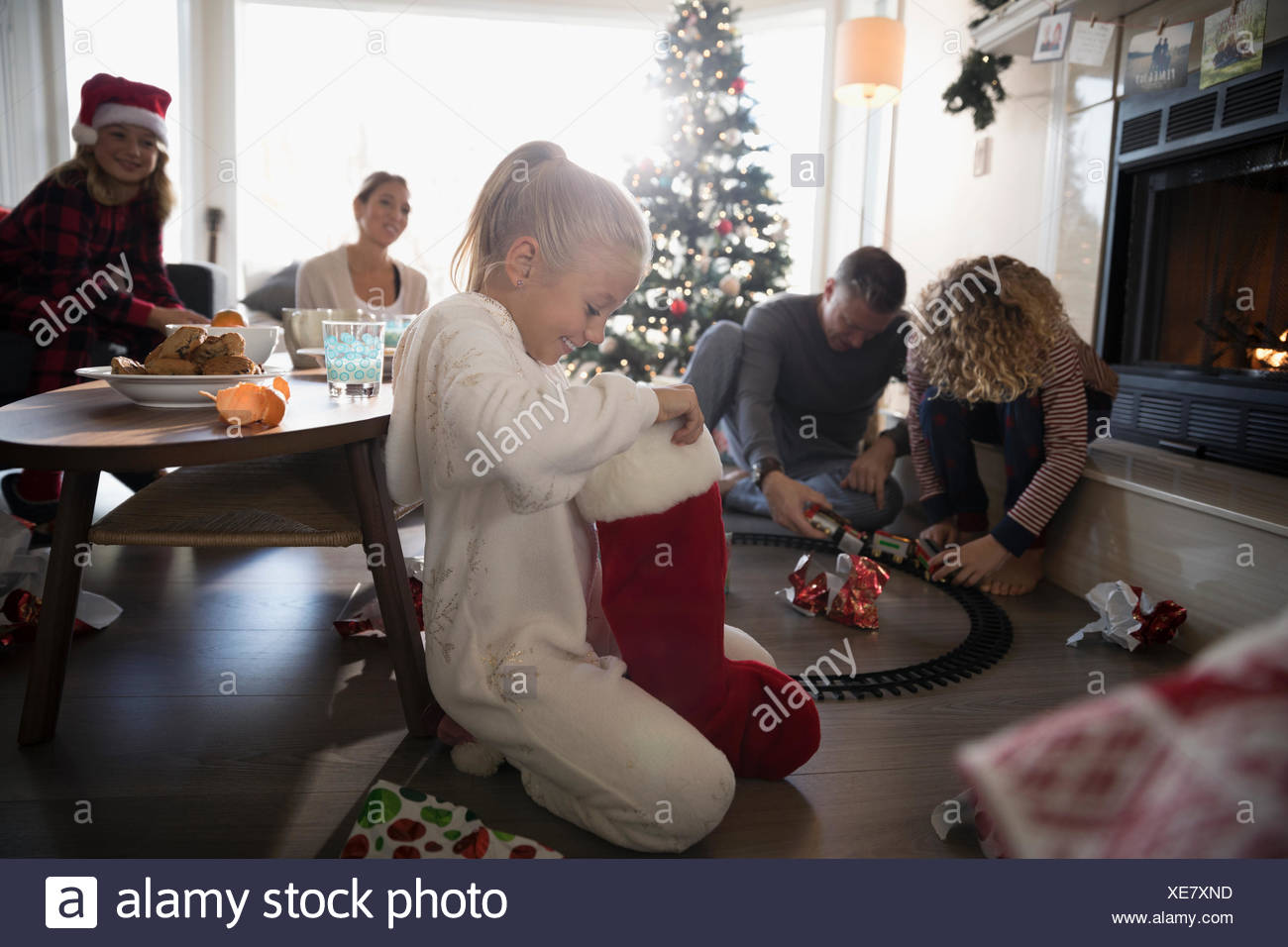 Girl in pajamas opening Christmas stocking with family in living room - Stock Image