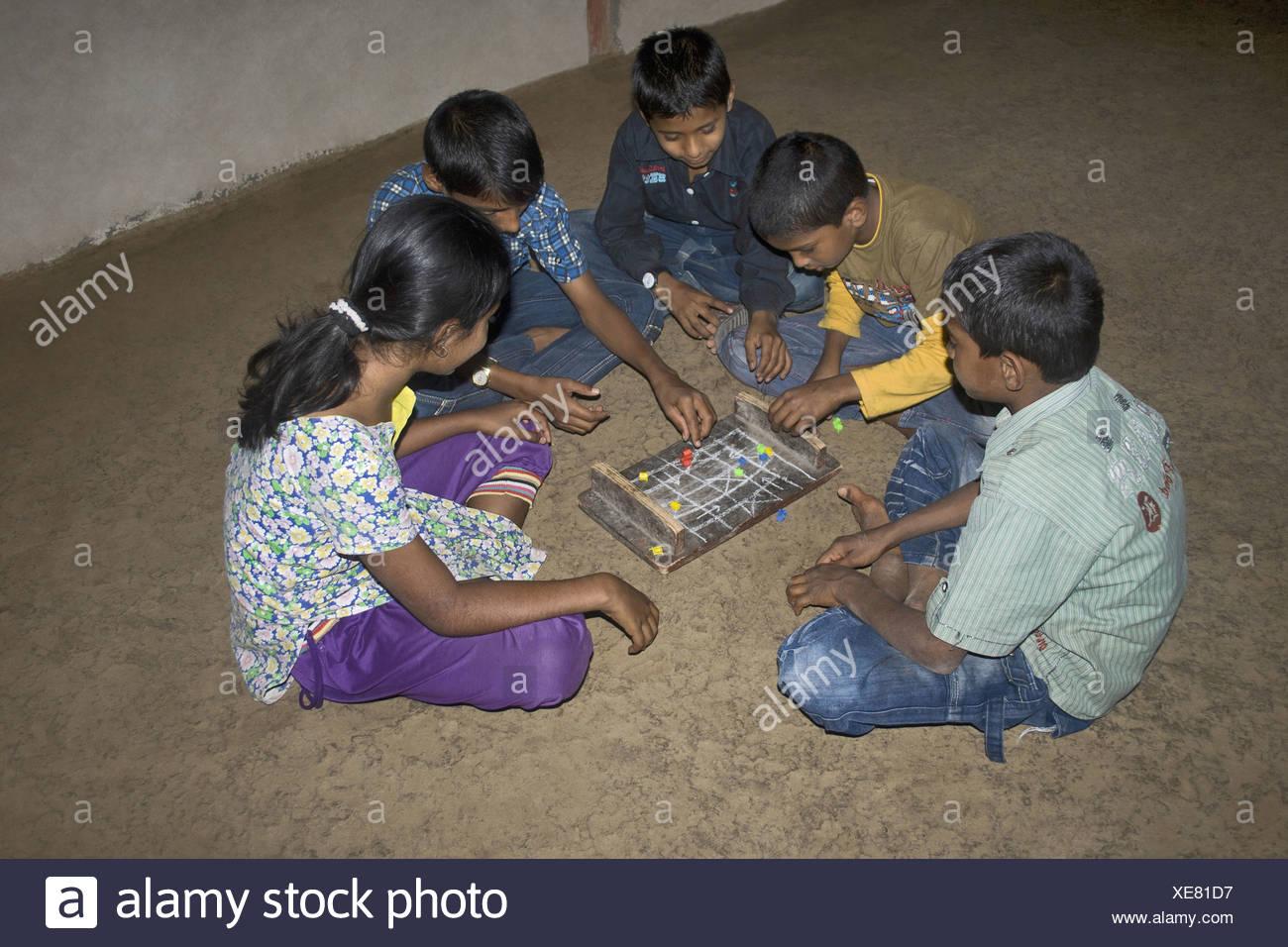 Children playing indoor game Pat (Ludo), Pabal, Pune, Maharashtra, India Stock Photo