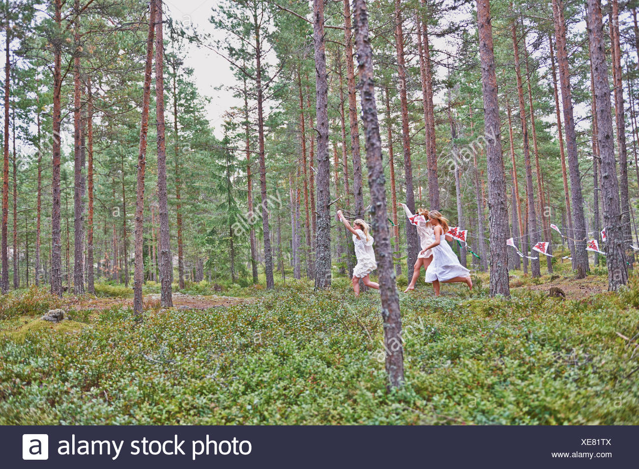 Teenage girls running in forest with kites Stock Photo