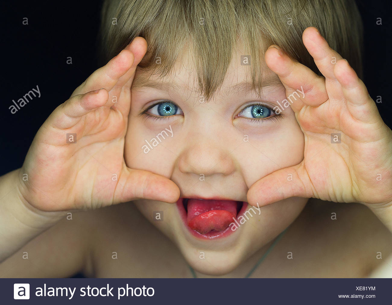 Little boy (4-5) looking at light from darkness - Stock Image