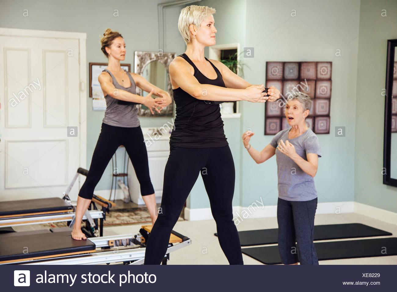 Women in gym using pilates reformer Stock Photo