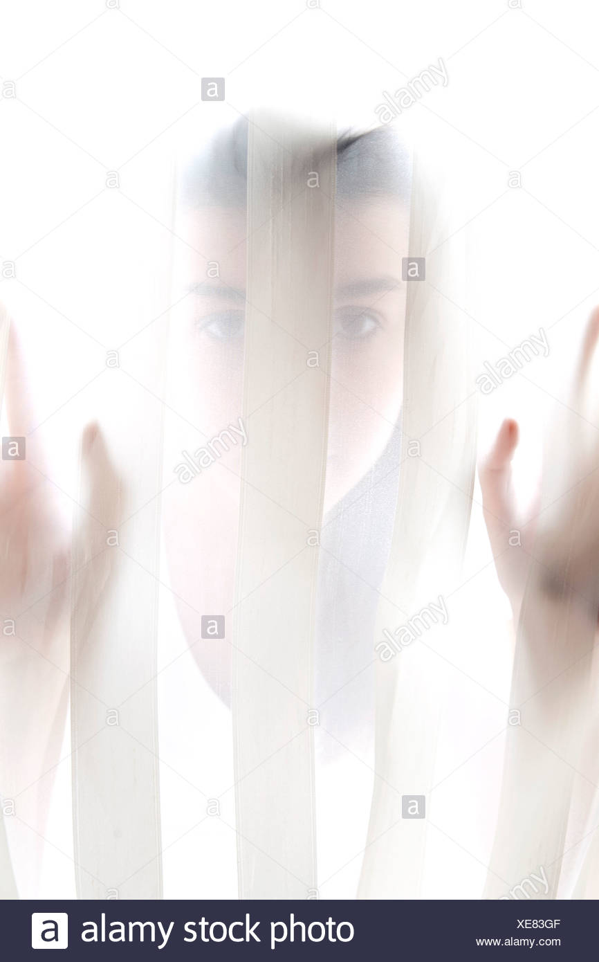 portrait of teenage girl behind curtain - Stock Image