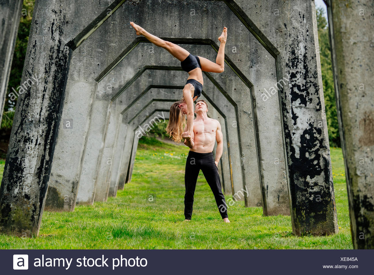 Young woman balancing on top of man hands, practicing yoga below concrete bridge - Stock Image