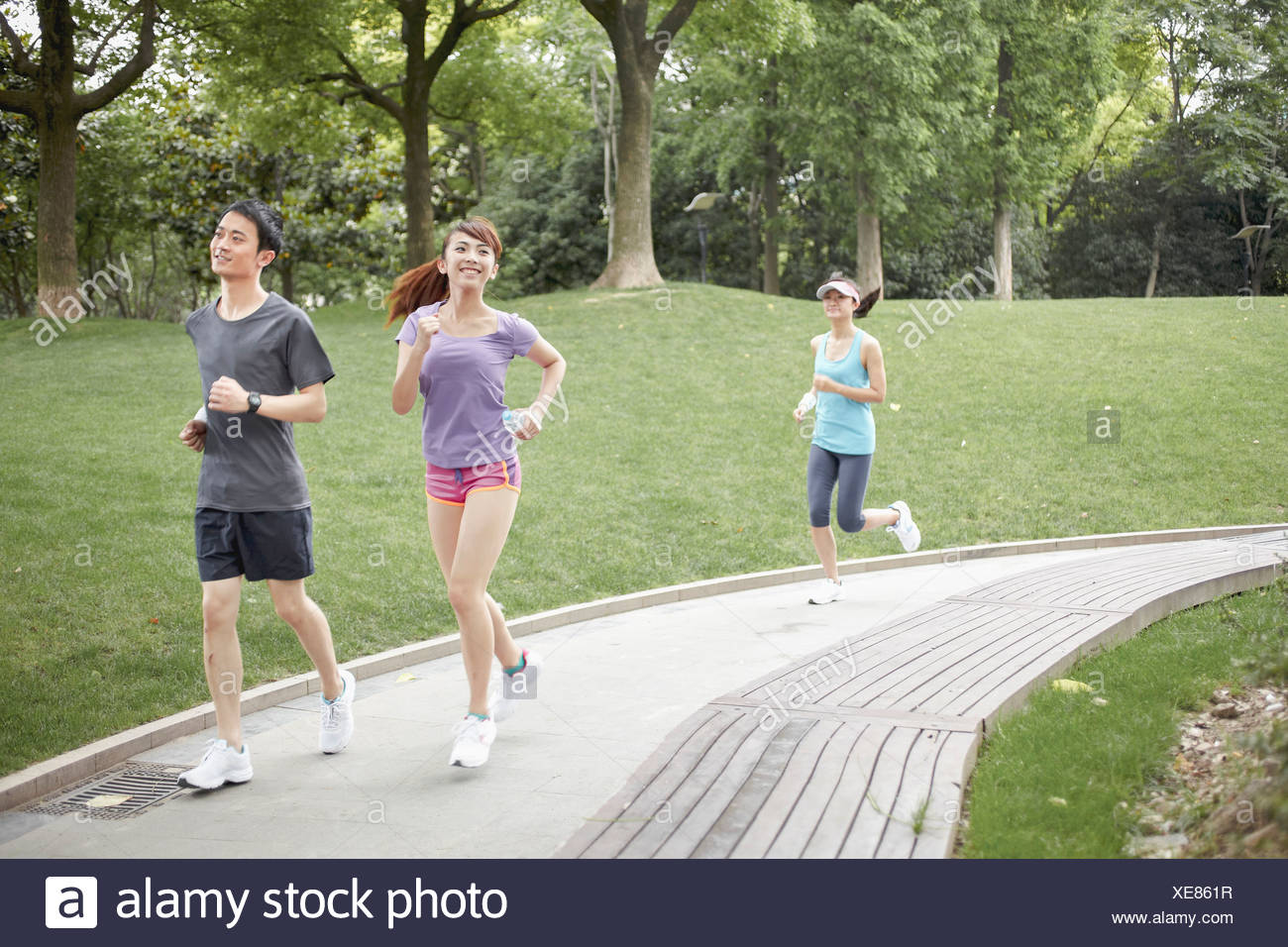 Three runners on path in park - Stock Image