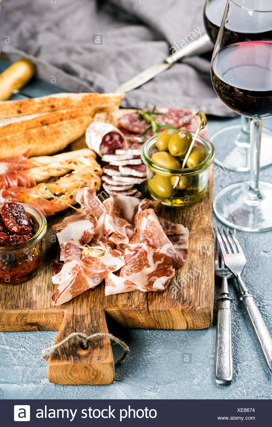 Meat appetizer selection. Salami, prosciutto, bread sticks, baguette, olives and sun-dried tomatoes, two glasses of red wine ove - Stock Image