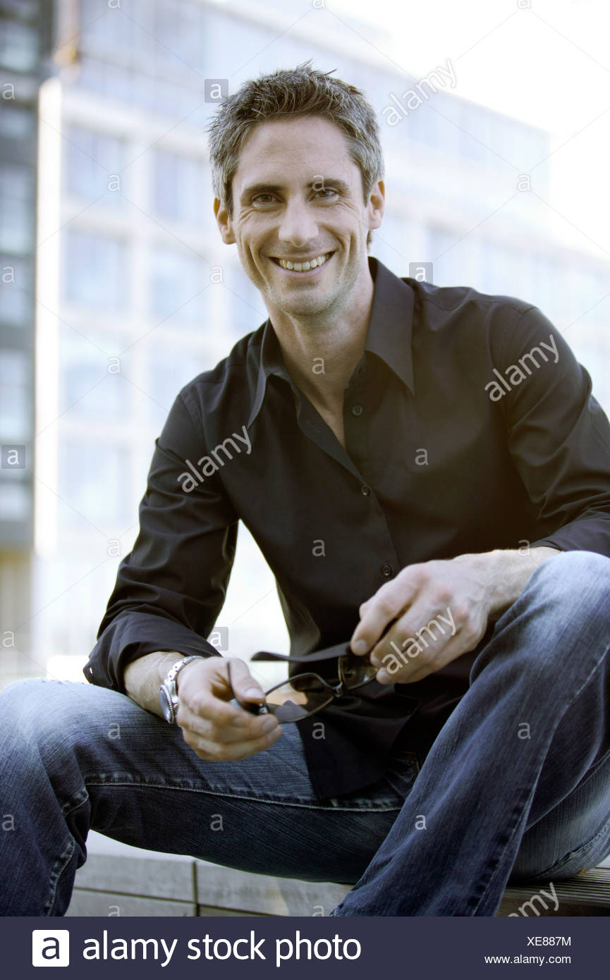 Man in black shirt with glasses - Stock Image