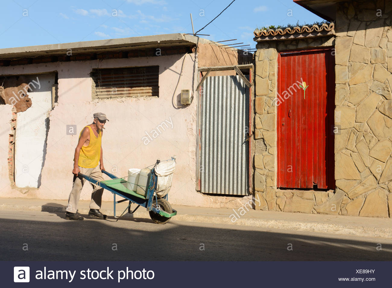 Man pushes wheelbarrow, Trinidad,  Cuba Stock Photo