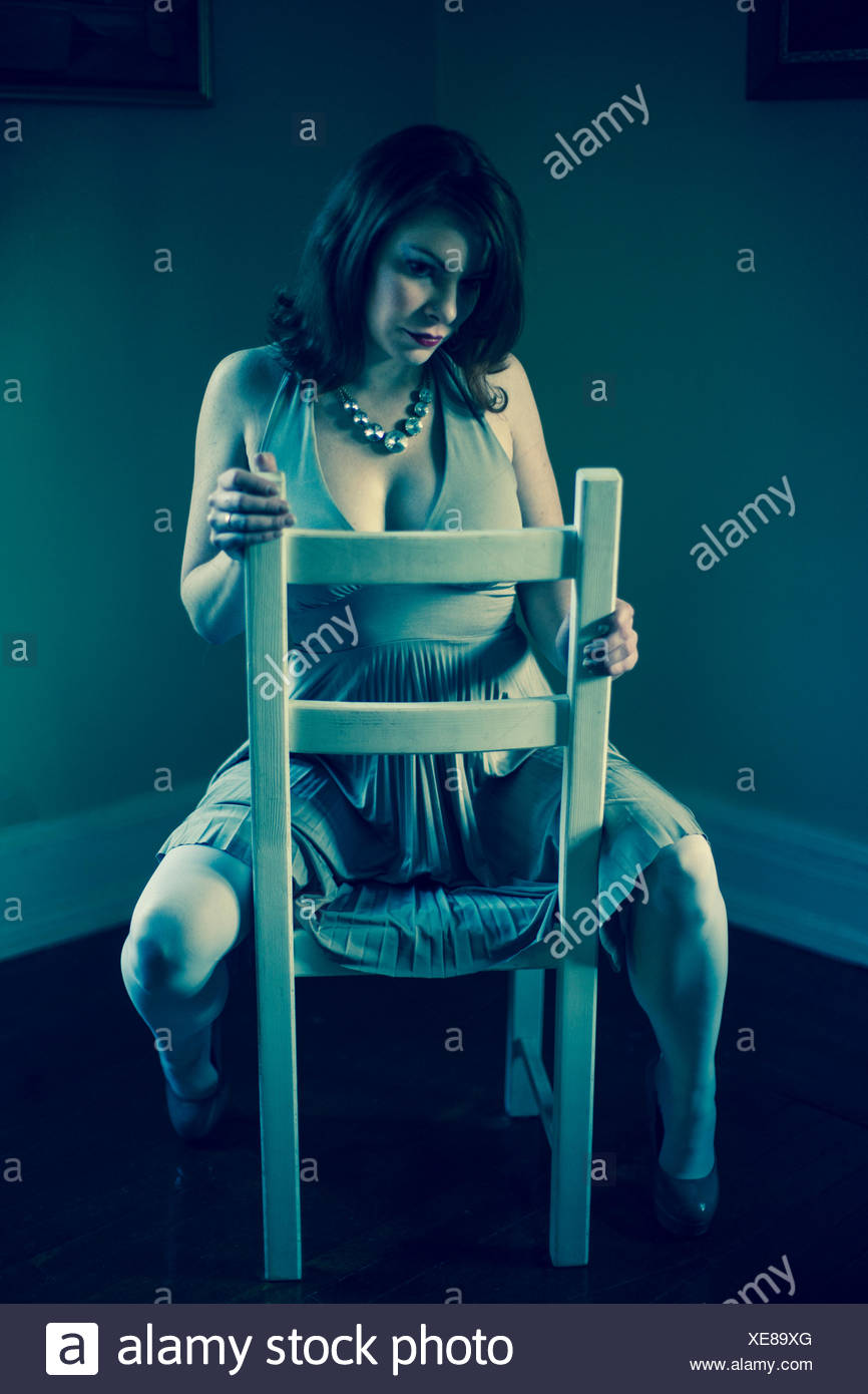 Portrait of mid adult woman, straddling chair - Stock Image