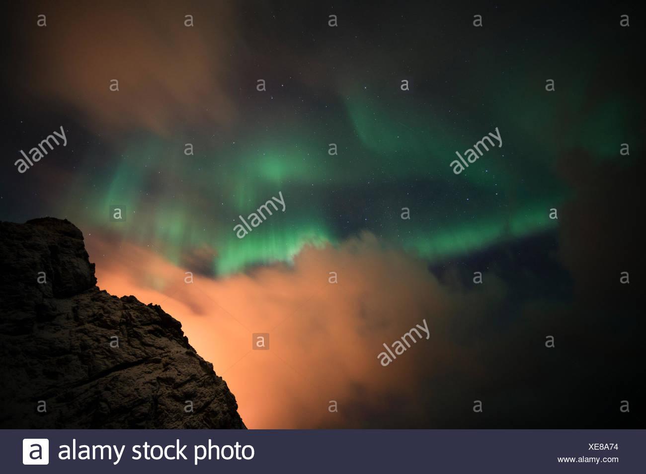 An aurora borealis behind a mountain peak in Andenes. - Stock Image