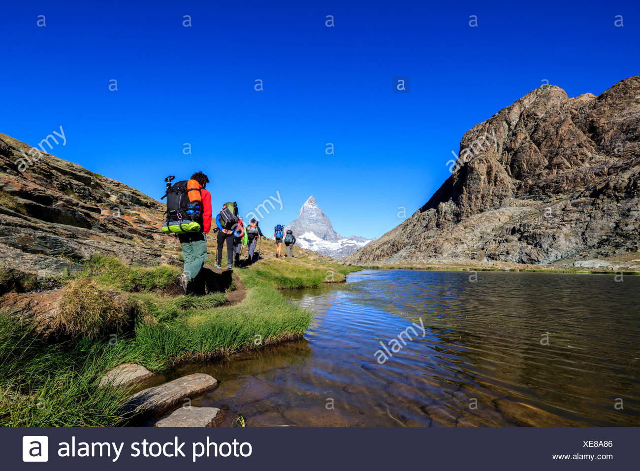 Hikers proceed on the shore of Lake Riffelsee with Matterhorn in the background Zermatt Canton of Valais Switzerland Europe - Stock Image