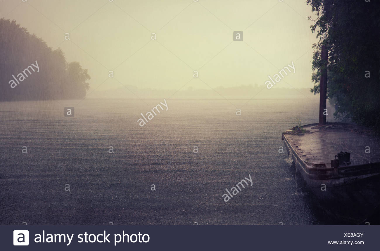 rain on the lake and old boat photo - Stock Image
