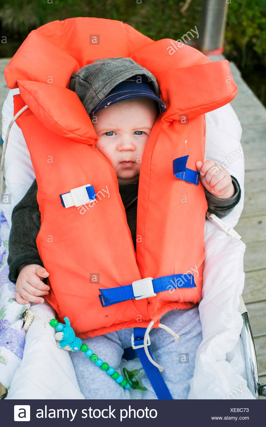 Sweden, Portrait of baby boy (6-11 months) in life jacket - Stock Image