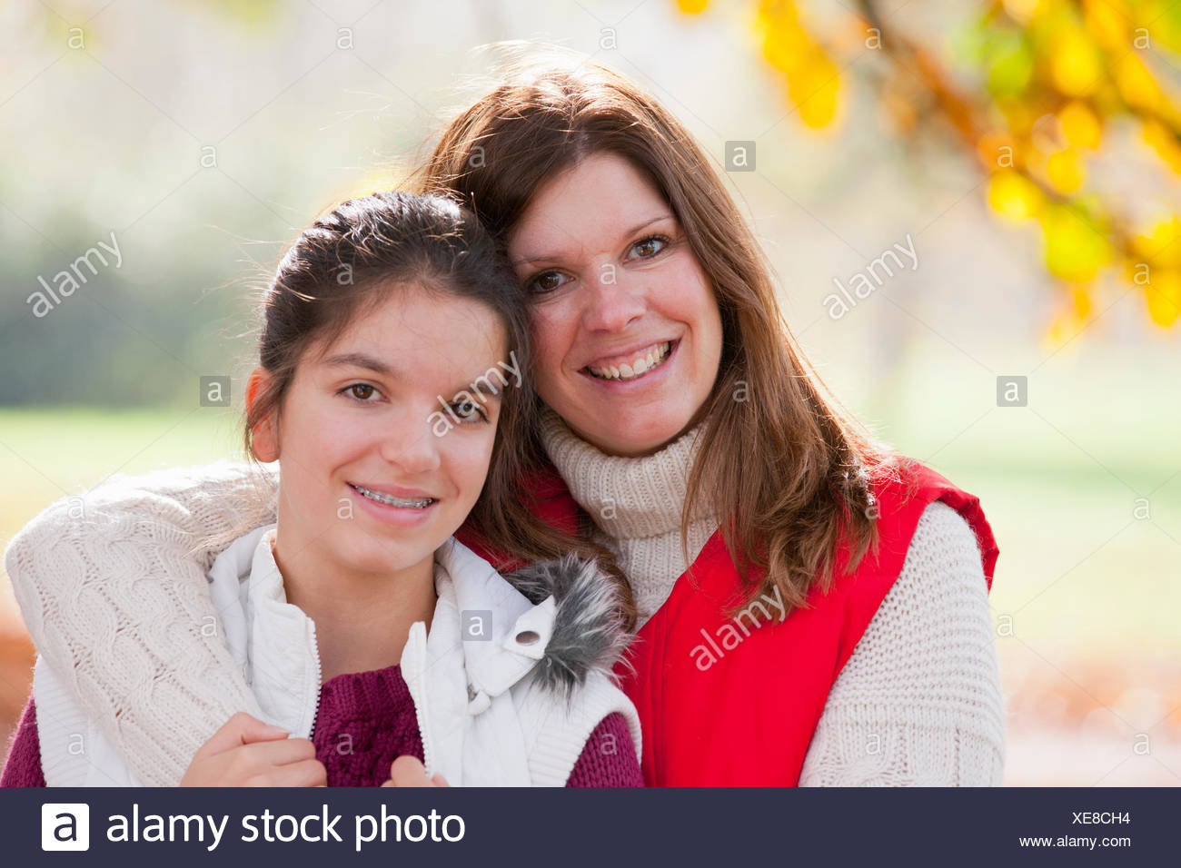 Mother with arm around daughter, looking at camera, in autumal park - Stock Image